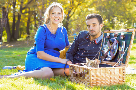 people relaxing: Pregnant happy and smiling couple on picnic with cat on sunny day