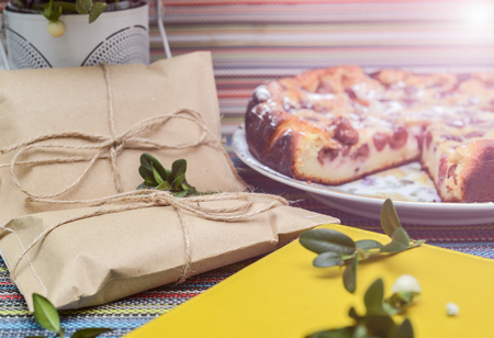 gold table cloth: notepad, paper envelope and piece of pie on the colorful tablecloth. sunlight Stock Photo