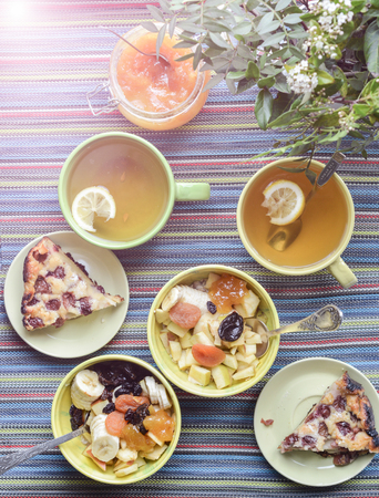 mush: breakfast with cereal mush, fruits, pie and tea for two. On the colorful tablecloth.