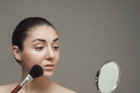 cheekbones: Beautiful girl looking in the mirror and applying cosmetic with a big brush. Girl gets blush on the cheekbones. Stock Photo
