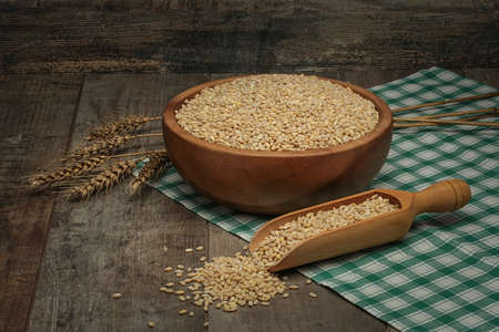 wooden scoop: Barley in a wooden bowl on wood with a scoop and wheat
