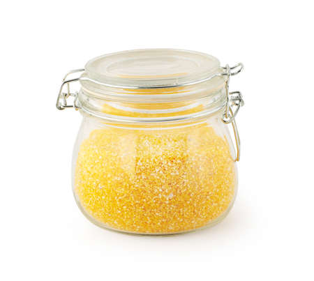 grits: glass jar with maize grits on white background