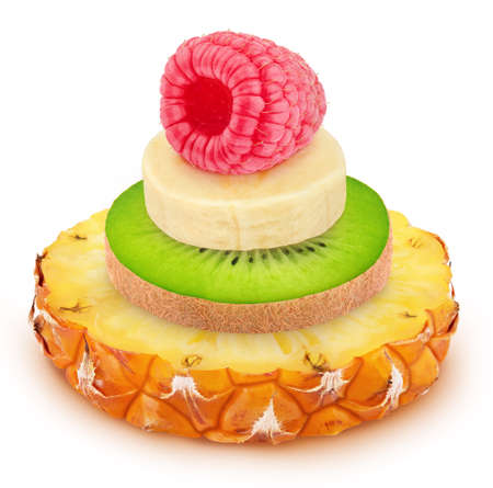 Creative composition with heap of fruit slices of pineapple, kiwi and banana with a raspberry on a topisolated on a white background. Raw eating concept.