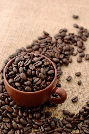 Cup with coffee beans and sacking background