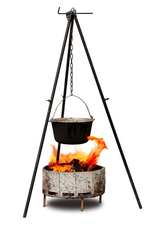 Cooking in old cast-iron on tripod isolated over white Stock Photo