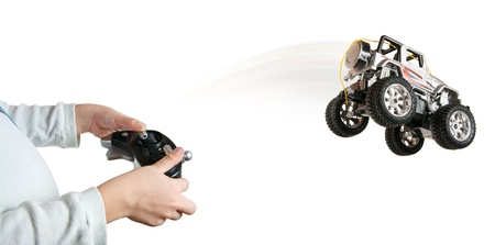 Little boy with remote control makes toy car to jump Stock Photo