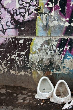 Grunge urban scene with graffiti and old urinals Stock Photo