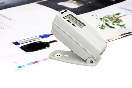 overprint: Measuring color density with densitometer on offset printed sheet Stock Photo
