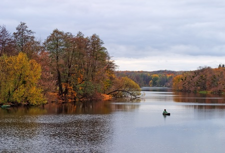 Autumnal landscape with river and fisherman photo
