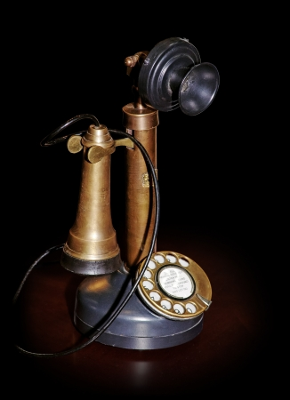 old microphone: Vintage phone on table isolated on black (pure black edges on picture) with clipping path Stock Photo