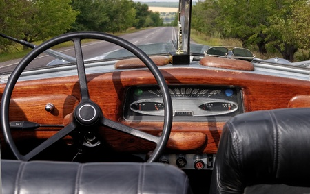 Wheel and dashboard of a old car photo