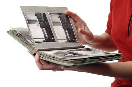 Woman looking in old photo album with black and white photos isolated on white photo