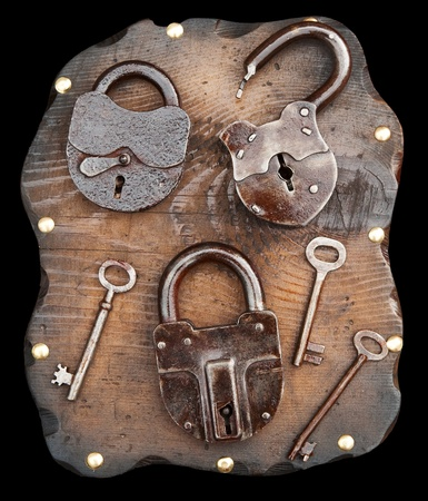 Old locks and keys on wooden plank isolated photo