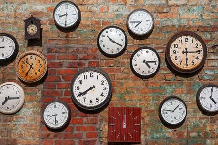 orologi antichi: Vecchi orologi sul muro di mattoni Archivio Fotografico