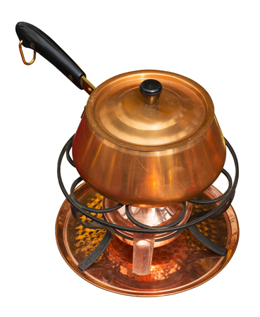 Copper pan on burner isolated on white. Clipping path included.