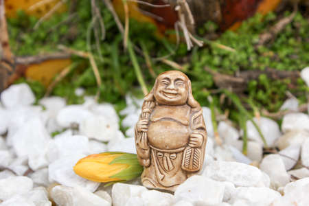 budda: Yellow flower with budda figurine composition with stones Stock Photo