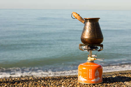 middle eastern food: Turk with coffee on a gas burner on the seafront
