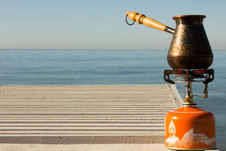 gas burner: Turk with coffee on a gas burner on the seafront