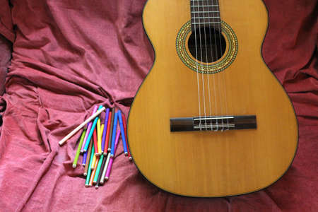 headstock: acoustic guitar and colored markers on the couch Stock Photo