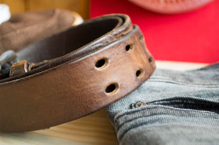 rough leather belt on jeans background and wood