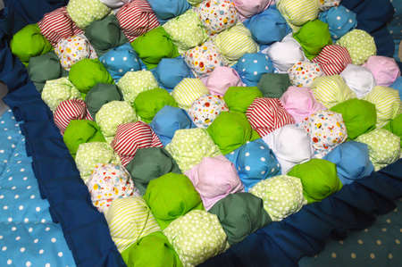 stitched stuffed blanket for babies on a wood background Stock Photo