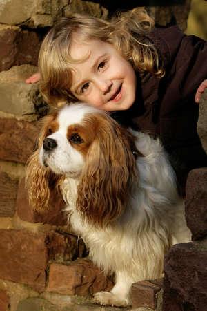 little blond girl hugging her spaniel dog
