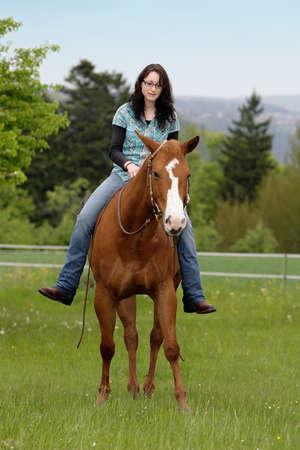vrouw astraddle haar Quarterhorse