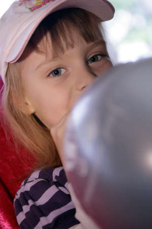 blow up: little kaukasian girl blow up a balloon Stock Photo
