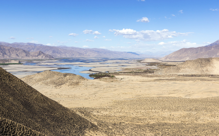 Typical landscape of Tibet - Holy Brahmaputra river, also known as Yarlung Tsangpo, desert and mountain landscape - Tibet