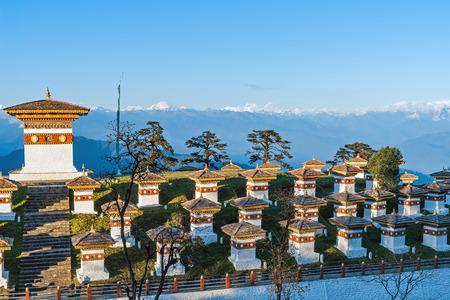Zonsondergang op Dochula Pass met Himalaya op achtergrond - Bhutan. In deze pass zijn 108 herdenking chortens of stupa's bekend als Druk Wangyal Chortens gebouwd door Ashi Dorji Wangmo Wangchuk.