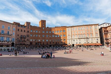 Unidentified tourists sunbathing on Piazza del Campo in Siena - Italy. Piazza del Campo is the principal public space of the historic center of Siena. Editorial