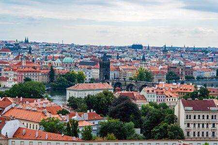 Charles bridge, Saint Nicolas church and roofs of Prague on a bright day - Prague, Czech Republic Editorial