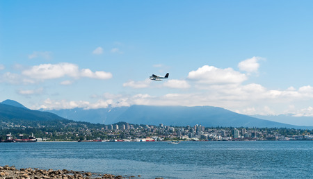 Seaplane taking off over Vancouver Bay with city skyline and snow mountains in background - Vancouver, British Columbia, Canada. Editorial