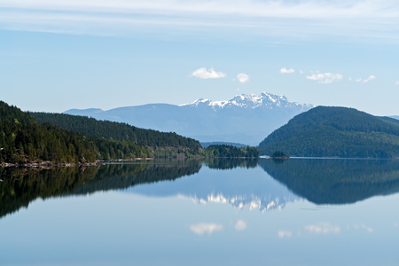 Snowy mountains reflection in a charming lake - Vancouver island, British Columbia, Canada Stock Photo