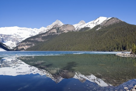 Snowy mountain reflection on half frozen lake Louise - Banff , Alberta, Canada. Shot was taken in late spring.