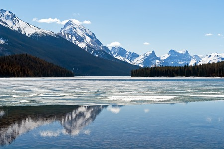 Snow covered Rocky mountains peaks reflected on the half frozen Maligne lake - Jasper national park, Alberta, Canada. The shot was taken in late spring. Stock Photo