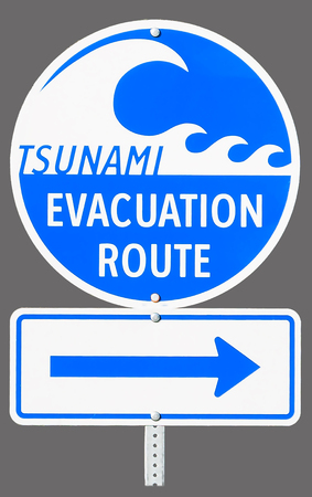 A highway sign marking Tsunami Evacuation Route in Vancouver Island - British Columbia, Canada. Close up of isolated sign on grey background. Stock Photo