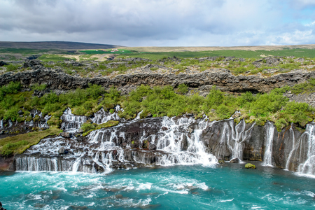 Hraunfossar waterfalls - Western Iceland. The water seems to appear from the lava but is a spring that surges through the ground and runs in rapids into the Hvita River.