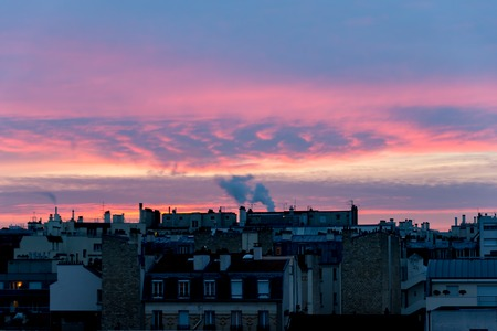 Sunrise over Paris roofs in winter with clouds and smoking chimneys - France Stock Photo
