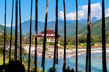 Punakha Dzong with prayer flags in foreground - Bhutan. Punakha Dzong Fortress is known as the Queen of Dzongs