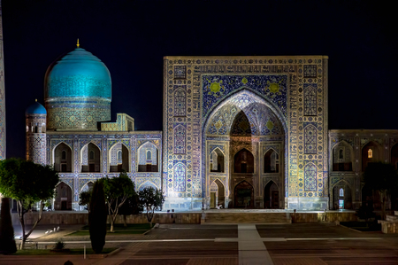Tilya-Kori Madrasah in Registan square at night - Samarkand, Uzbekistan - It has a two-storied main facade and a vast courtyard fringed by dormitory cells, with four galleries along the axes.