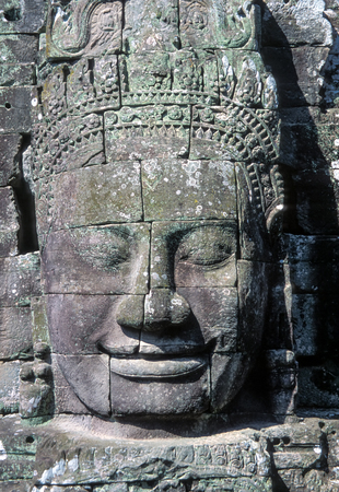 Stone Faces of Bayon Temple in Angkor Wat - Cambodia. There are some 50 towers around the ruined temple, with over 200 faces showing varying degrees of erosion and wear.