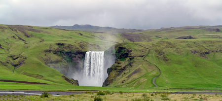 Skogafoss waterfall - Skogar village, South Iceland. The Skogafoss is one of the biggest waterfalls in the country with a width of 15 metres and a drop of 60 m. Stock Photo