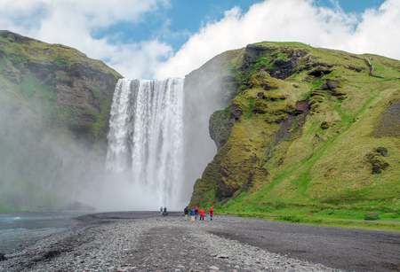 Tourists in walking to Skogafoss waterfall - South Iceland. The Skogafoss is one of the biggest waterfalls in the country with a width of 15 metres and a drop of 60 m.