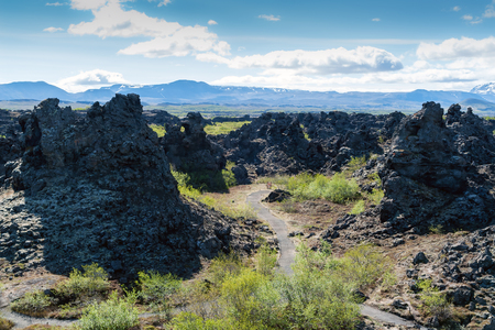 Footpath in Dimmuborgir lava field, Myvatn area - Iceland. The Dimmuborgir area is composed of various volcanic caves and rock formations, reminiscent of an ancient collapsed citadel.