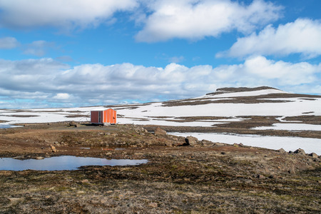 Red emergency shelter cabin standing in the mountain near Seydisfjordur - Iceland