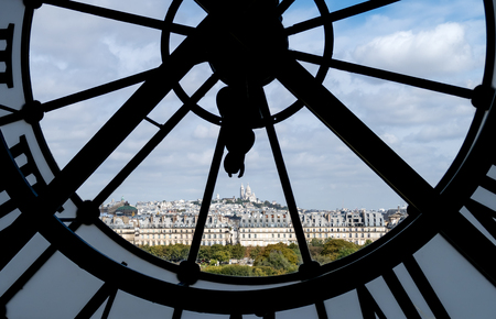 Paris cityscape through the giant glass clock at the Musee dOrsay with view on the Tuileries Garden, Palais royal, Opera Garnier, Sacre-Coeur and Montmartre hill - Paris, France Editorial