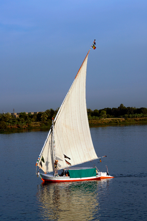 Felucca at dusk with white sails, sailing along the Nile River - Egypt Stock Photo