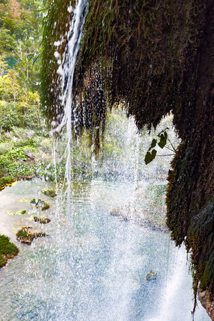 Waterfalls in Plitvice National Park - Croatia. Overlooking from behind a waterfall.
