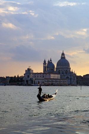 Gondola with Santa Maria della Salute in Venice at sunset - Italy Editorial